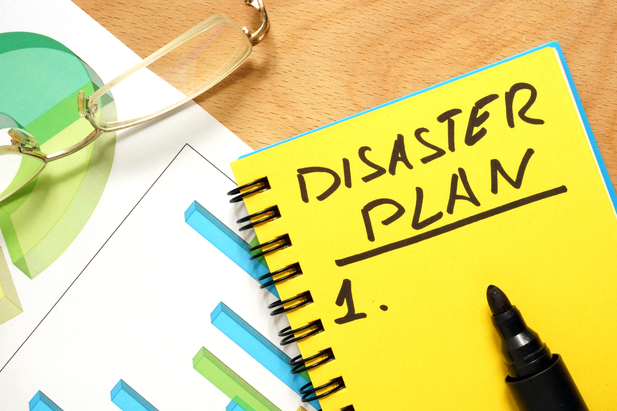 Notepad with disaster plan on a wooden table