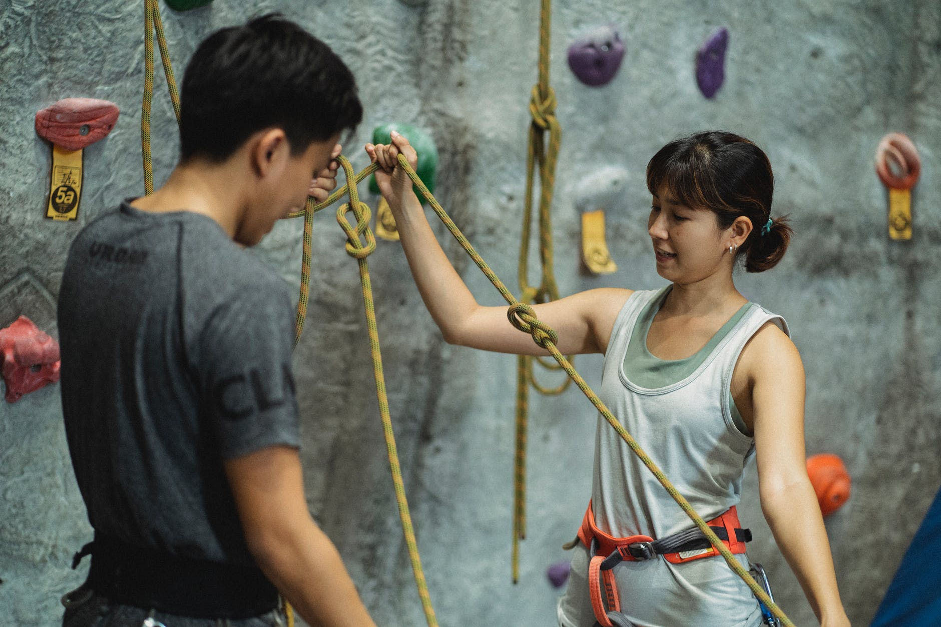 unrecognizable instructor interacting with asian mountaineer while preparing safety ropes