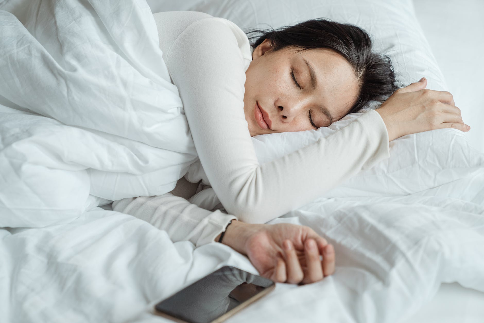 woman sleeping in bed near smartphone