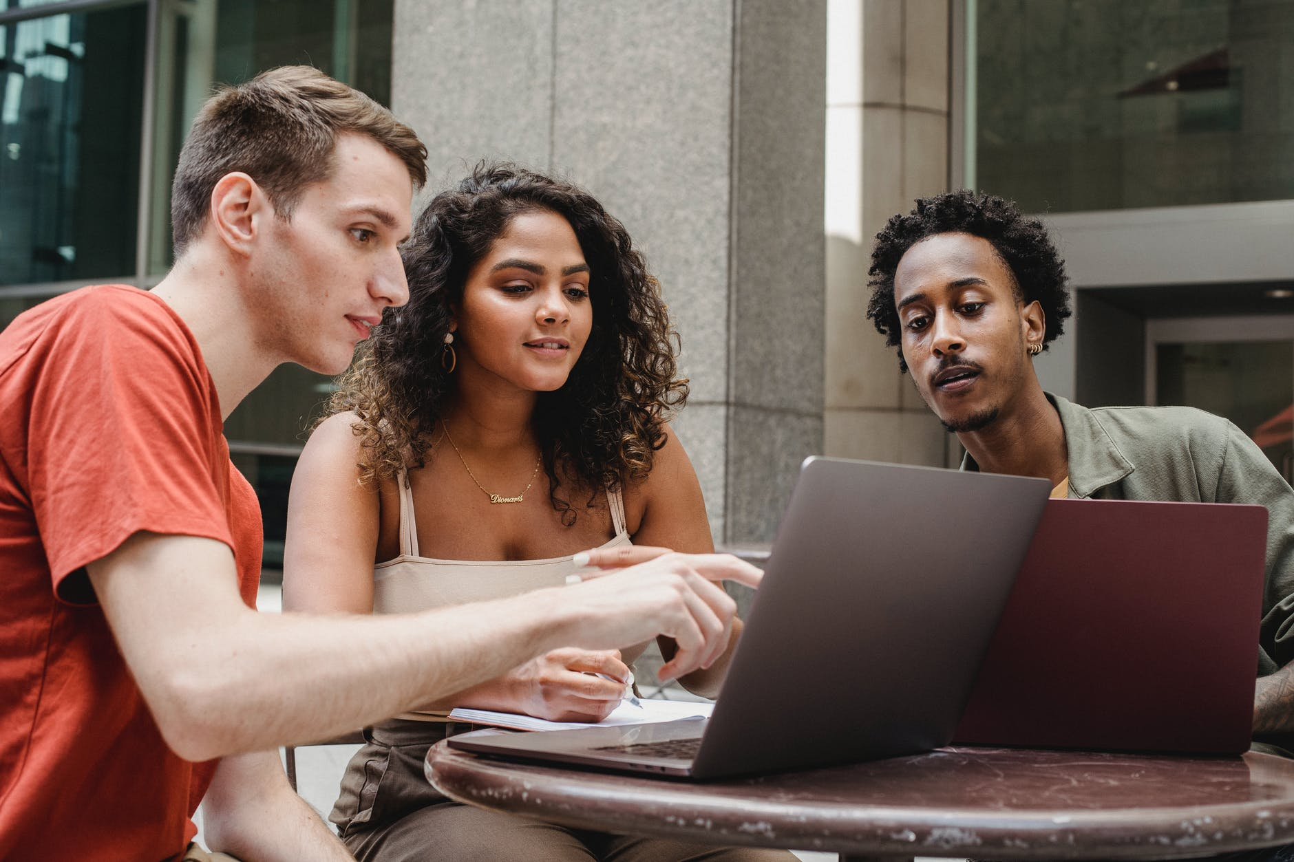group of multiethnic coworkers discussing startup project on laptops together